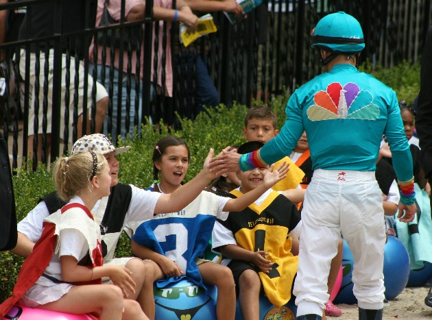 Del Mar Camp kids waiting to start the hippty hop race on the track get high-fived from a jockey.