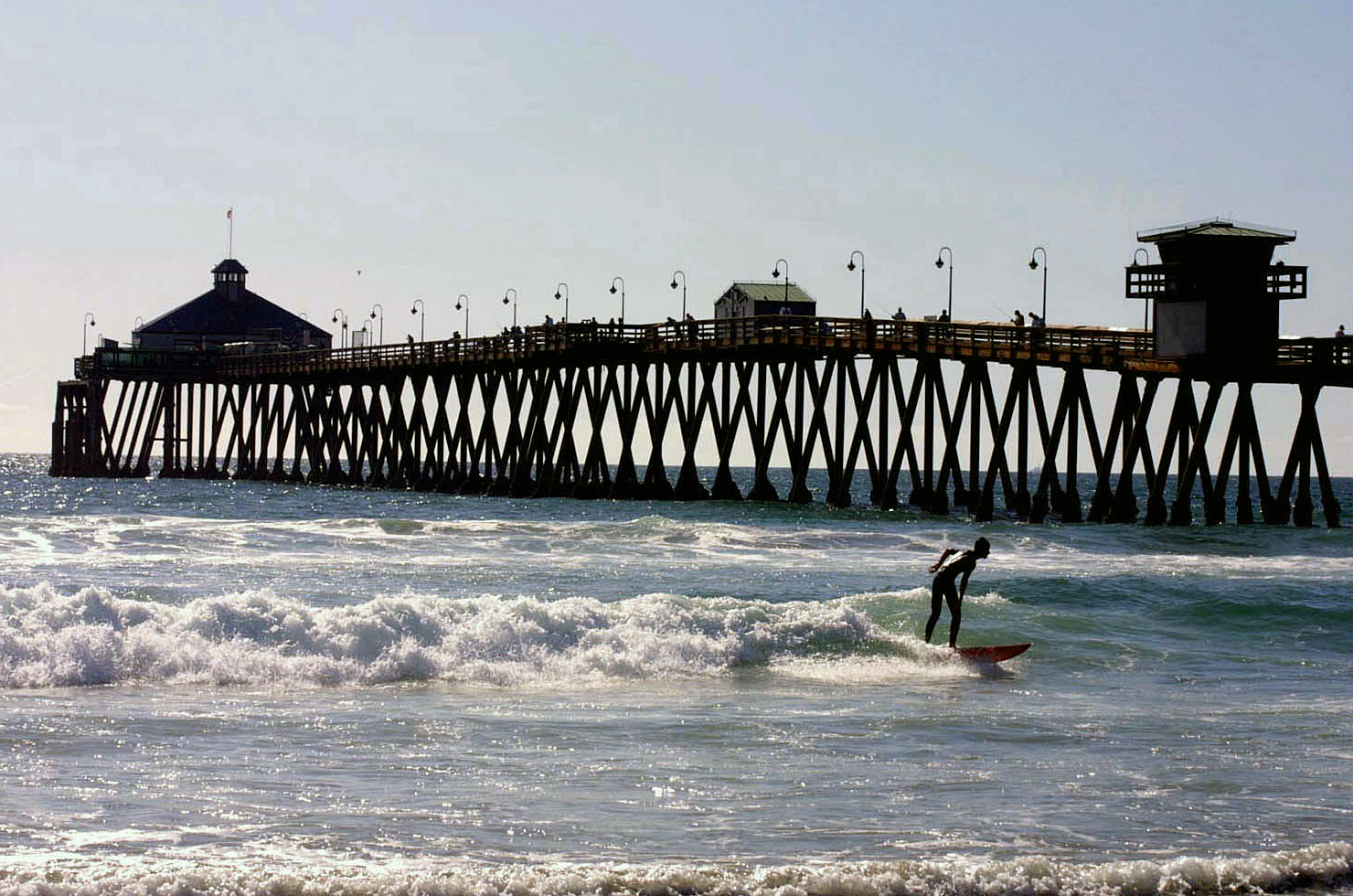 Surfer in front of Imperial Beach Pier in San Diego's South Bay