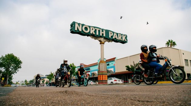 Moped riding past the North Park sign - Top Things to Do in San Diego